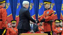 Outgoing RCMP chief William Elliott shakes hands with new Commissioner Bob Paulson during a change-of-command ceremony in Ottawa on Dec. 8, 2011. (Sean Kilpatrick/Sean Kilpatrick/The Canadian Press)