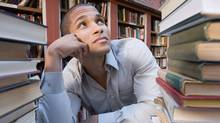 Student looking up at a stack of books. (Jupiterimages/Getty Images)