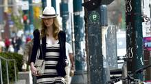 """The """"real-way"""" model struts down the street in her striped maxi dress. (Fred Lum/Fred Lum / Globe and Mail)"""