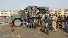 A Canadian army truck loaded with school supplies is overrun by children at Camp Shirzai in Kandahar on Jan. 18, 2007. (MURRAY BREWSTER/THE CANADIAN PRESS)