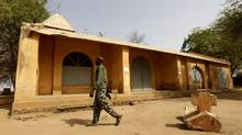 A Malian soldier walks away from a cross, believed to have been removed by Islamist rebels from the church seen in the background, in the recently liberated town of Diabaly Jan. 24, 2013. (ERIC GAILLARD/REUTERS)