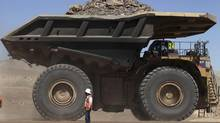 A mining truck loaded with rocks and minerals travels past a worker along a road at Chile's Esperanza copper mine near Calama town, about 1,650 km (1,025 miles) north of Santiago, March 30, 2011. (IVAN ALVARADO/REUTERS)
