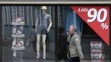 A man passes a shop advertising a closing down sale in Riga (INTS KALNINS)