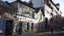 A pedestrian walks past graffiti covered buildings in Dublin, Ireland, in 2013. (Simon Dawson/Bloomberg)