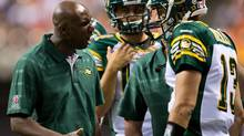 Edmonton Eskimos' head coach Kavis Reed, left, shouts at quarterback Mike Reilly after he came off the field after failing to gain the first down against the B.C. Lions during the second half of a CFL game in Vancouver, B.C., on Saturday July 20, 2013. (DARRYL DYCK/THE CANADIAN PRESS)