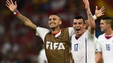 Chile's Arturo Vidal, left, and Gary Medel celebrate at the end of their 2014 World Cup Group B soccer match against Spain at the Maracana stadium in Rio de Janeiro June 18, 2014. (Dylan Martinez/REUTERS)