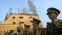 NANJING, CHINA - SEPTEMBER 23: Members of a military band wait to perform in front of the replica of the treasure ship sailed by Chinese navigator Zheng He (1371-1435), at the Zheng He Treasure Boat Factory Ruins Park launching ceremony on September 23, 2006 in Nanjing of Jiangsu Province, China. (China Photos/Getty Images)