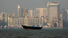 A fishing boat passes the Taj Mahal hotel in Mumbai. The price of homes in or near the city puts them out of reach for most middle-class Indians. (© Jayanta Shaw/REUTERS)