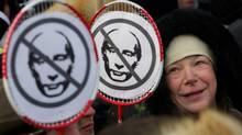 A Russian woman smiles beside images of Russian Prime Minister Vladimir Putin held by protesters in Moscow on Feb. 4, 2012. (Ivan Sekretarev/AP)