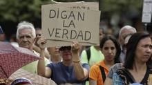 "An opponent of Venezuela's President Hugo Chavez holds up a sign that reads in Spanish, ""Tell the truth,"" during an outdoor gathering in Caracas, Venezuela, Saturday, Jan. 12, 2013. Venezuelan opposition politicians say they're preparing to present a case before a regional human rights court to challenge a Supreme Court decision that permits the indefinite postponement of Chavez's inauguration. (Ariana Cubillos/AP)"