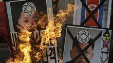 South Korean protesters in Seoul burn pictures of North Korean leader Kim Jong-un following the North's third nuclear test, Feb. 12, 2013. (Lee Jin-man/AP)