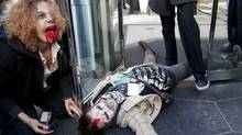 A member of the Occupy Vancouver movement lays on on the ground at the front doors of the Embridge offices during a Zombie Walk throughout downtown Vancouver, B.C. Monday, Oct. 31, 2011. The Zombie walk included stops at banks and oil and gas companies. (Jonathan Hayward/The Canadian Press/Jonathan Hayward/The Canadian Press)