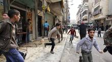 People run upon hearing a nearby plane bombing during a protest against Syrian President Bashar al-Assad in the al-Katerji Tariq district in Aleppo on Feb. 22, 2013. (MUZAFFAR SALMAN/REUTERS)