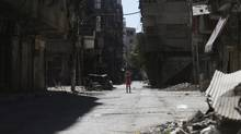 A girl stands in a damaged street in Ain Tarma, in Eastern Ghouta, a suburb of Damascus, on Aug. 21, 2014. The death toll from three years of Syria's civil war has risen to more than 191,000 people, the United Nations reported Friday. (BASSAM KHABIEH/REUTERS)