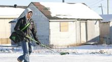 A youth walks past a boarded up house in the Ontario First Nations community of Attawapiskat on Nov. 29, 2011. The community has long grappled with a housing crisis. (ADRIAN WYLD/THE CANADIAN PRESS)