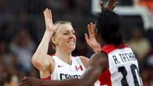 Canada's Lizanne Murphy (L) celebrates with teammate Alisha Tatham after sinking in her 3-point shot during the women's Group B basketball match against Russia at the London 2012 Olympic Games in the Basketball arena July 28, 2012. (SERGIO PEREZ/REUTERS)