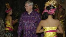 "Canadian Prime Minister Stephen Harper, wearing an ""endek,"" a traditional Balinese woven-fabric garment, arrives for a dinner for leaders of the Asia-Pacific Economic Cooperation (APEC) forum in Bali, Indonesia, Monday, Oct. 7, 2013. (Dita Alangkara/AP)"