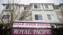 "A real estate sign reading ""Sold Over Asking"" stands on display outside a townhouse in Richmond, British Columbia, Canada, on Sunday, Dec. 11, 2016. (Ben Nelms/Bloomberg)"