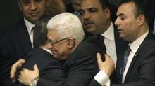 Palestinian Authority President Mahmoud Abbas, right, is embraced by Turklish Foreign Minister Ahmet Davutoglu after a UN vote on upgrading the Palestinian Authority's status to non-member observer state, Nov. 29, 2012. (Kathy Willens/AP)
