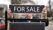 A broker puts up a 'for sale' sign before an open house in Toronto. (Darren Calabrese For The Globe and Mail)