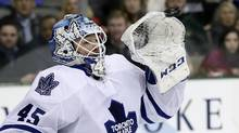 Toronto Maple Leafs goalie Jonathan Bernier reaches up to glove a shot from the Dallas Stars in the first period of an NHL hockey game, Thursday, Jan. 23, 2014, in Dallas. (Tony Gutierrez/AP)