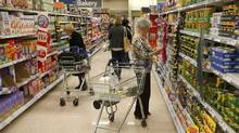 Customers shop for groceries in a supermarket in London October 18, 2011. Inflation in Britain hit a three-year high in September driven by soaring gas and electricity bills, further eroding living standards and piling more pressure on the government to help struggling consumers. (STRINGER/UK/Reuters)