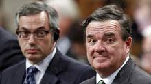 Finance Minister Jim Flaherty and Treasury Board President Tony Clement stand to vote in the House of Commons on June 12, 2012. (CHRIS WATTIE/REUTERS)