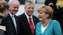Germany's Chancellor Angela Merkel is greeted by Northern Ireland's First Minister Peter Robinson, centre, and Deputy First Minister Martin McGuinness as she arrives to attend the Enniskillen G8 summit, at Belfast International airport, June 17, 2013. (PETER MUHLY/REUTERS)