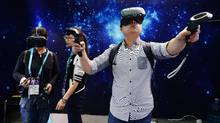 This photo taken on May 11, 2016 shows visitors trying wearable virtual reality devices during the first day of the Consumer Electronics Show (CES) in Asia in Shanghai. (STR/AFP/Getty Images)