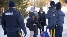 RCMP officers arrest an asylum claimant and her two daughters after crossing the border into Canada from the United States, on March 17, 2017, near Hemmingford, Que. (Paul Chiasson/THE CANADIAN PRESS)