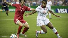North Korea's Ri Hyang Sim, left, hangs on to Canada's Ashley Lawrence's jersey as they battle for possession of the ball during their U-20 Women's World Cup match in Montreal on Tuesday. (Paul Chiasson/THE CANADIAN PRESS)