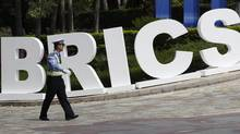 A traffic policeman walks past a signage decoration for BRICS Summit outside the Sheraton Hotel, the venue of BRICS Summit in Sanya, China's Hainan province, April 13, 2011. (JASON LEE/REUTERS)