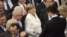 German Chancellor Angela Merkel, centre, and other lawmakers cast their ballots during the vote for ratification of the European Union fiscal pact in Berlin June 29, 2012. (FABIAN BIMMER/Reuters)
