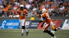 B.C. LionsÕ quarterback Kevin Glenn, (2) passes to Andrew Harris (33) as Hamilton Tiger-CatsÕ Craig Butler defends during the first half of a CFL football game in Vancouver, B.C., on Friday August 8. (DARRYL DYCK/THE CANADIAN PRESS)