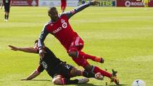 Toronto FC's Ashtone Morgan battles for the ball with DC United's Danny Cruz (L) during the second half of their MLS soccer match in Toronto, May 5, 2012. (Reuters)