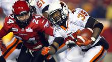 B.C.Lions' Tim Brown, right, tries to get past Calgary Stampeders' Keenan MacDougall during first quarter CFL football action in Calgary on Friday, Oct. 26, 2012. (The Canadian Press)