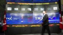 """TMX Broadcast Centre manager Kris Backus walks in front of the centre's display board in Toronto on Monday May 16, 2011. The homegrown group making a $3.6-billion proposal for TMX Group (TSX:X) says its Ðtruly Canadian"""" bid wouldn't mean job cuts or a management shakeup and the operator of the Toronto Stock Exchange would remain publicly traded. (Frank Gunn/Frank Gunn/The Canadian Press)"""