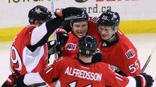 Ottawa Senators' Chris Neil (25) is congratulated by teammates Jason Spezza (19) Sergei Gonchar (55) and Daniel Alfredsson (11) after scoring during first period NHL hockey action against the Florida Panthers in Ottawa Thursday December 22, 2011. (FRED CHARTRAND/THE CANADIAN PRESS)