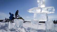 Kiefer Sterriah and Archie Erigaktuk head back to Dechinta University by snowmobile as they pass an inukshuk after ice fishing April 17, 2014. (John Lehmann/The Globe and Mail)