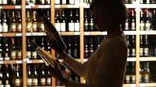 An employee looks over bottles of white wine at a wine store in Penticton, B.C. October 3, 2006. (JOHN LEHMANN/GLOBE AND MAIL)