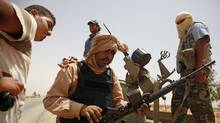 Libyan rebels try to fix a rifle near the front line outside the village of Tiji in western Libya, July 31, 2011. (BOB STRONG/REUTERS)