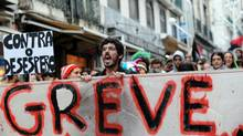 "A protester holds a banner reading ""strike"" as he takes part in a demonstration in downtown Lisbon on November 24, 2010. Portugal's first mass general strike in more than two decades brought the country to a halt today to protest spending cuts the government says are vital to avoid financi"