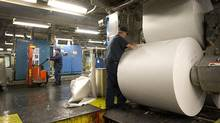 An employee feeds paper into a printing press at the Toronto Star printing plant in Toronto, Ontario, Canada, on Wednesday, July 6, 2011. (Brent Lewin/Bloomberg)