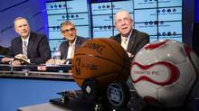 BCE CEO George Cope, left, Rogers CEO Nadir Mohamed and Larry Tanenbaum, chairman of MLSE, announce the sale of the sports company in Toronto Dec. 9, 2011. (MARK BLINCH/REUTERS)