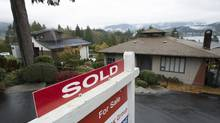 A sold sign is seen outside a home in North Vancouver, B.C. Thursday, Oct. 27, 2016. A proposed tax would see homeowners pay one per cent of the assessed value of non-principal residences they do not rent out. The tax will go before city council next week. (JONATHAN HAYWARD/THE CANADIAN PRESS)