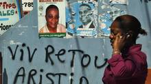 """A Haitian woman uses her mobile phone next to a poster of Haiti's presidential candidates Mirlande Manigat and a graffiti that reads """"Welcome Aristide"""" in Port-au-Prince March 17, 2011. (Eduardo Munoz/Reuters/Eduardo Munoz/Reuters)"""