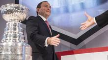 NHL Commissioner Gary Bettman prepares to shake an extended hand at a news conference in Toronto on Tuesday 26, 2013. (Chris Young/THE CANADIAN PRESS)