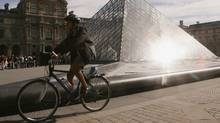 A woman rides a bicycle in front of the pyramid of the Louvre museum on August 24, 2005 in Paris. (Pascal Le Segretain/Pascal Le Segretain/Getty Images)