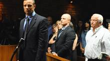 Olympian Oscar Pistorius stands following his bail hearing, as his brother Carl, centre, and father Henke look on, in Pretoria, South Africa. The family of Oscar Pistorius, the double-amputee Olympian charged with murdering his girlfriend, is feuding publicly about whether guns are a necessary protection against crime in South Africa. (Masi Losi/AP)