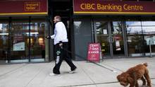 A person walks by a sign posted outside a CIBC branch in Toronto. (Michelle Siu For The Globe and Mail)